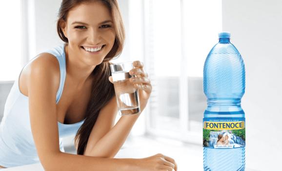 ragazza che beve acqua fontenoce con bottiglia a vista